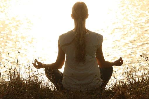 河原で瞑想する女性