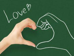 黒板に書かれた手と自分の手を合わせる