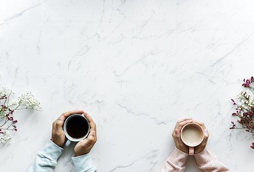 マグカップに手を添える男女の手元