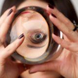 水晶玉で顔が反転して映っている占い師