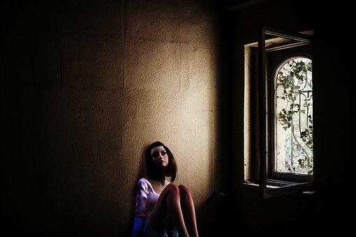 暗い部屋で1人座り込む女性