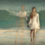 海岸で彼の幻影を感じる女性