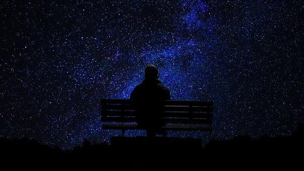 ベンチから夜空を眺める人