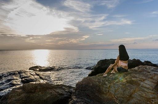 崖から海岸線を眺める人
