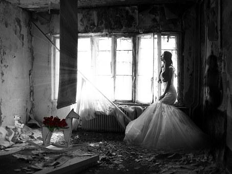 部屋で1人ウエディングドレス姿でたそがれる女性