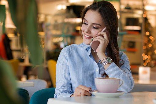カフェで電話するスーツ姿の女性