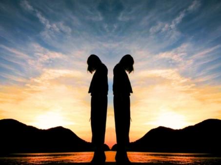 背中を向け合って佇む2人のシルエット