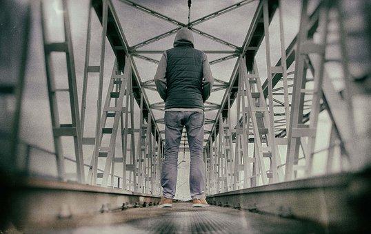 鉄骨の橋に佇む男性の後ろ姿