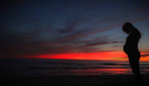 夕暮れの海岸に佇む妊婦