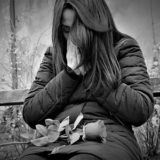 ベンチでバラを持って泣く女性