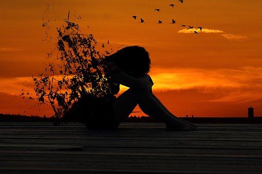 夕暮れ、ヒザを抱えて泣く女性
