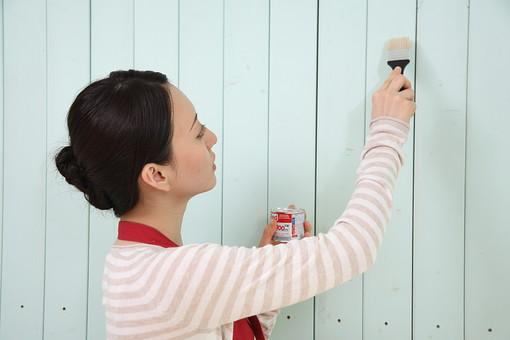 壁にペンキを塗るエプロン姿の女性