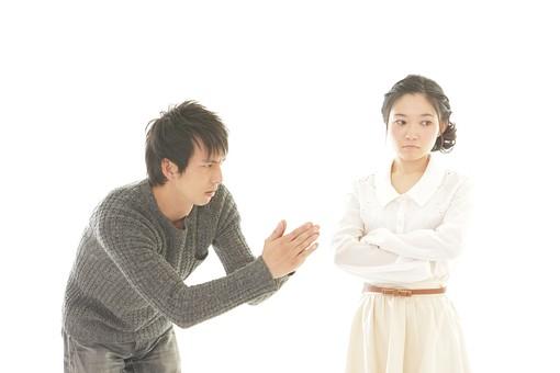 女性に手を合わせて謝る男性