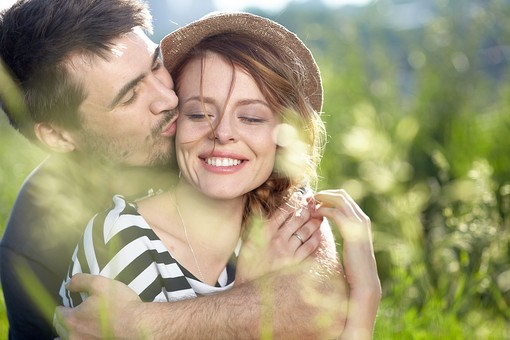 草原で彼女を抱きしめる男性