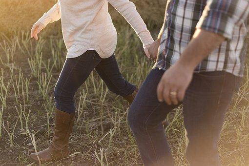草むらを手を繋いで歩く男女の足元