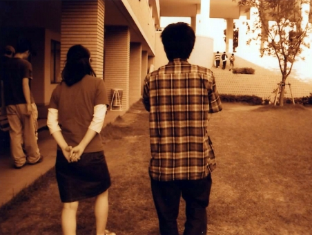 歩きながら話す男女の後ろ姿