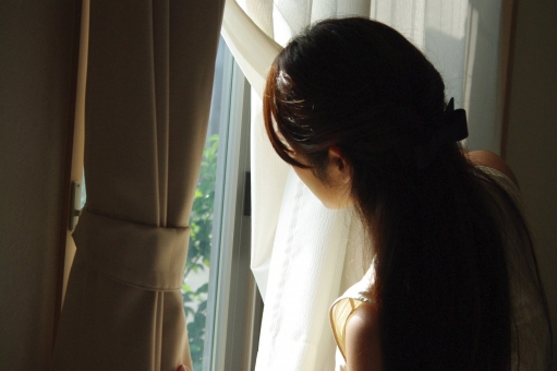 窓の外を窺う女性