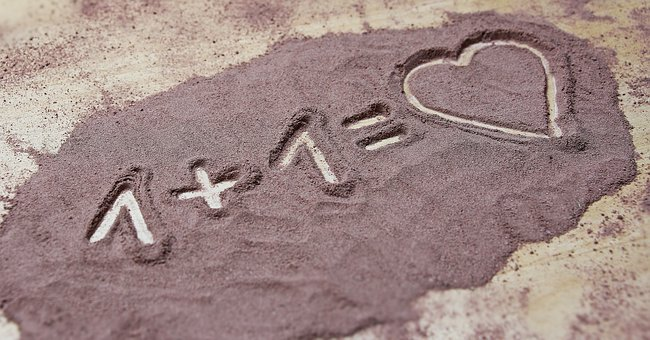 砂浜に書かれた1+1=♥