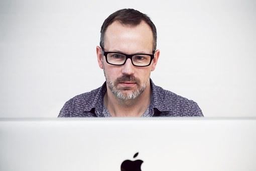 パソコンのモニターを眺める眼鏡の男性