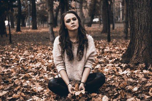 枯れ葉の上に胡座で座る女性