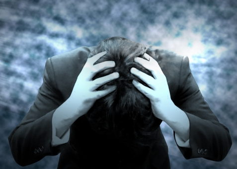 不安で頭を抱える男性