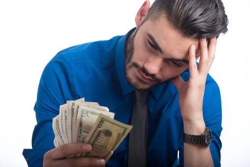 お金を持って悩む男性