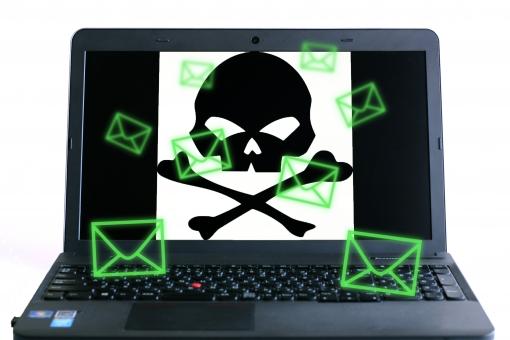 パソコン画面に映し出されたドクロと迷惑メール