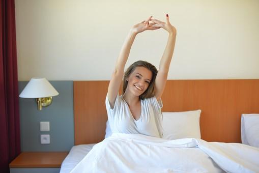 寝起きに笑顔で伸びをする女性