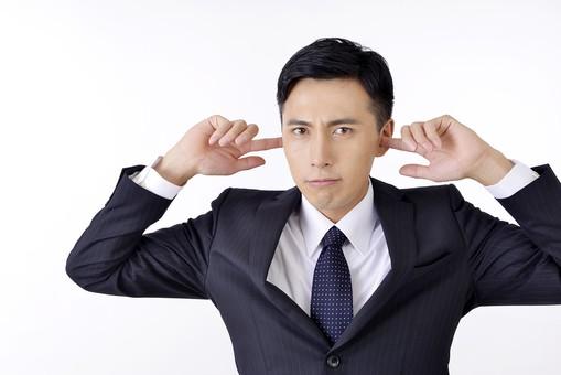 耳を塞ぐサラリーマン男性