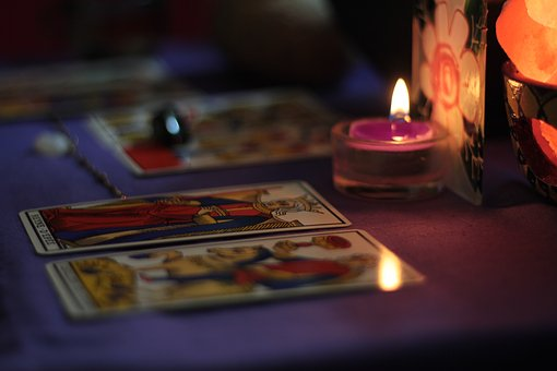 暗い部屋にあるタロットカードと蝋燭