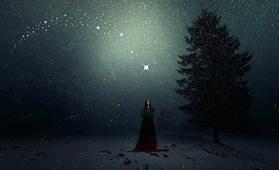 夜の丘で祈る女性