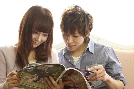 二人で雑誌を読むカップル