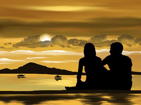 夕暮れのビーチで会話するカップル