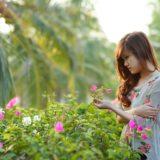 ピンクの花を見つめる女性