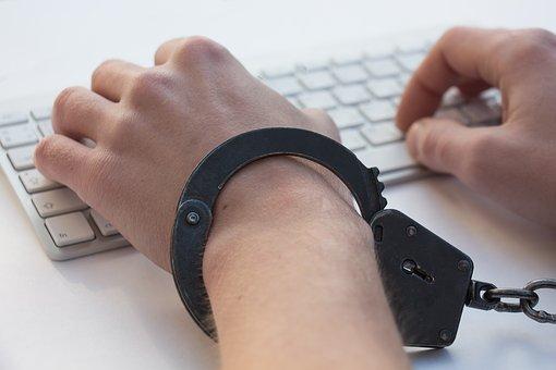 手錠した手でキーボードを叩く