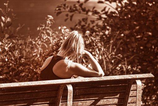 1人ベンチに座る寂しそうな女性