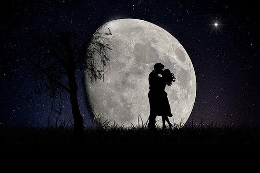 満月の夜に抱き合う男女の影