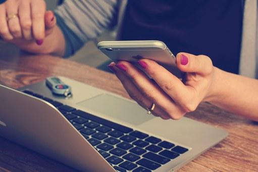 スマホとパソコンと女性の手