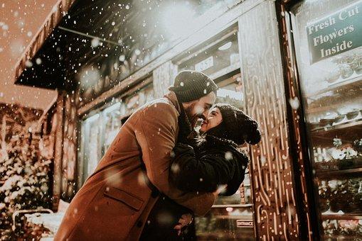 雪の降る中で抱きしめ合うカップル