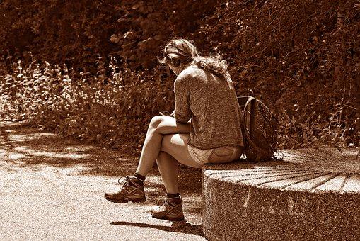 椅子に腰掛ける寂しそうな女性