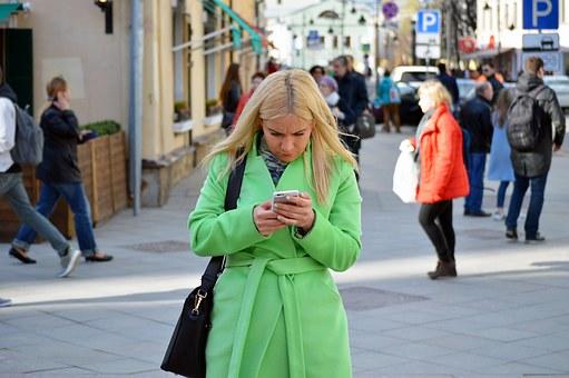 街の中でスマホを操作する女性