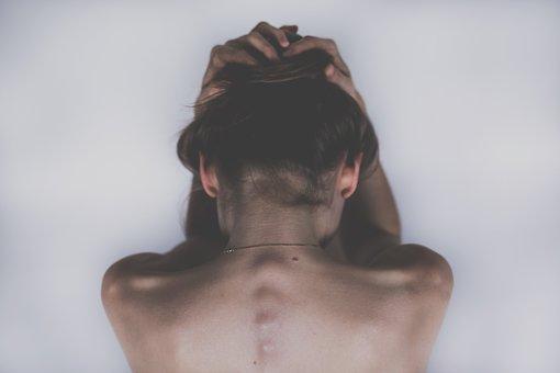 頭を抱えて悲しむ女性の後ろ姿