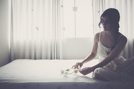 ベッドで花の冠を触る女性