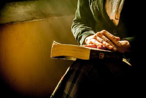 膝に置かれた聖書と女性の手元