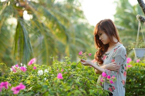 寂しそうに花を触る女性