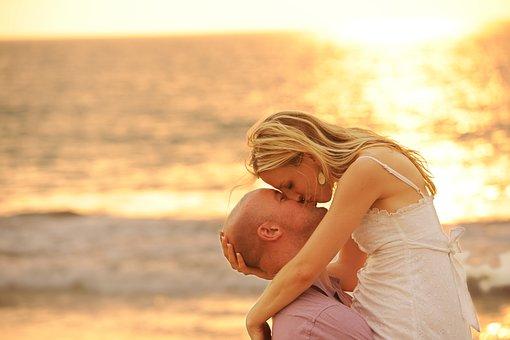 夕方のビーチでキスするカップル