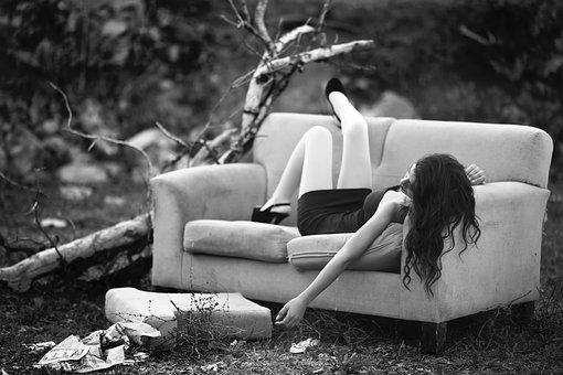 ソファーに寝転ぶ寂しそうな女性