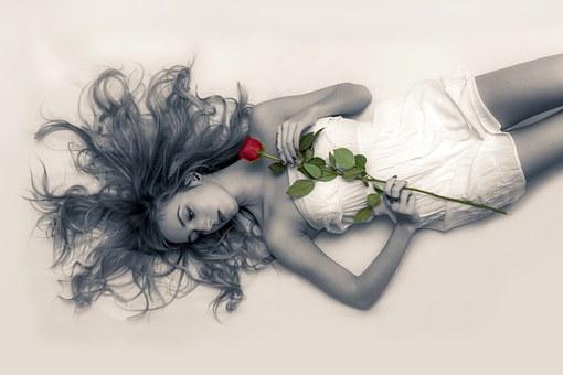 赤い薔薇を持った女性が寝ている
