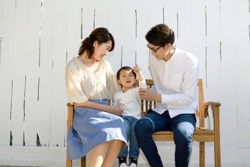 ベンチに座る3人家族