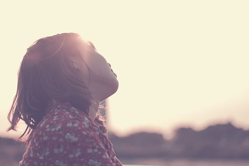 悲しそうに空を見上げる女性